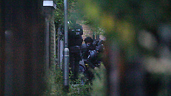© Licensed to London News Pictures . 26/07/2017 . Oldham , UK . Armed police sneak through a back alley behind the house and round to the front door to blow through the front door to end the siege in the early hours of the morning . Scene of an armed siege that began at 3.15am on Tuesday 25th July in a house on Pemberton Way in Shaw , is ongoing in to a second night . A man named locally as Marc Schofield is reported to be holding a woman hostage after earlier releasing two children . The gas supply in the area has been cut off and several neighbouring properties have been evacuated . Photo credit : Joel Goodman/LNP