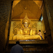 May 14, 2013 - Mandalay, Myanmar: Visitors pay respects to a gold casted statue at Mahamuni Buddha Temple in Mandalay. The city, famous for its pagodas, is a popular tourist destination for buddhist devotees from all over Southeast Asia. CREDIT: Paulo Nunes dos Santos
