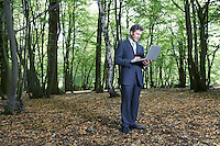 Business man standing in middle of forest typing on laptop