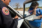 05 MAY 2003 -- SELLS, AZ:  A Tohono O'Odham police officer writes a speeding ticket for a women he stopped on for speeding on AZ 86 east of Sells, AZ, the capital of Tohono OOdham Indian Reservation, May 5, 2003. the officer found a family of six undocumented immigrants from Mexico in the back of the woman?s truck. The Tohono OOdham reservation covers a vast expanse of Southern Arizona and has a 70 mile border with Mexico. In recent years the reservation has been flooded with undocumented immigrants who pass through the reservation on their way north to Phoenix, AZ, and other cities in the US. About 1,500 undocumented immigrants, most from Mexico, cross the reservation, which has more land than the state of Delaware,  every day. According to the tribal government, the tribal police department spends about 60 percent of its resources dealing with crime created by the undocumented immigrants. Many times tribal police officers have to wait hours for the US Border Patrol to respond to calls to pick up undocumented immigrants. This family was released by the tribal police two hours after the Border Patrol was notified that the police had the family. The Border Patrol didn?t respond the tribal police call.  PHOTO BY JACK KURTZ
