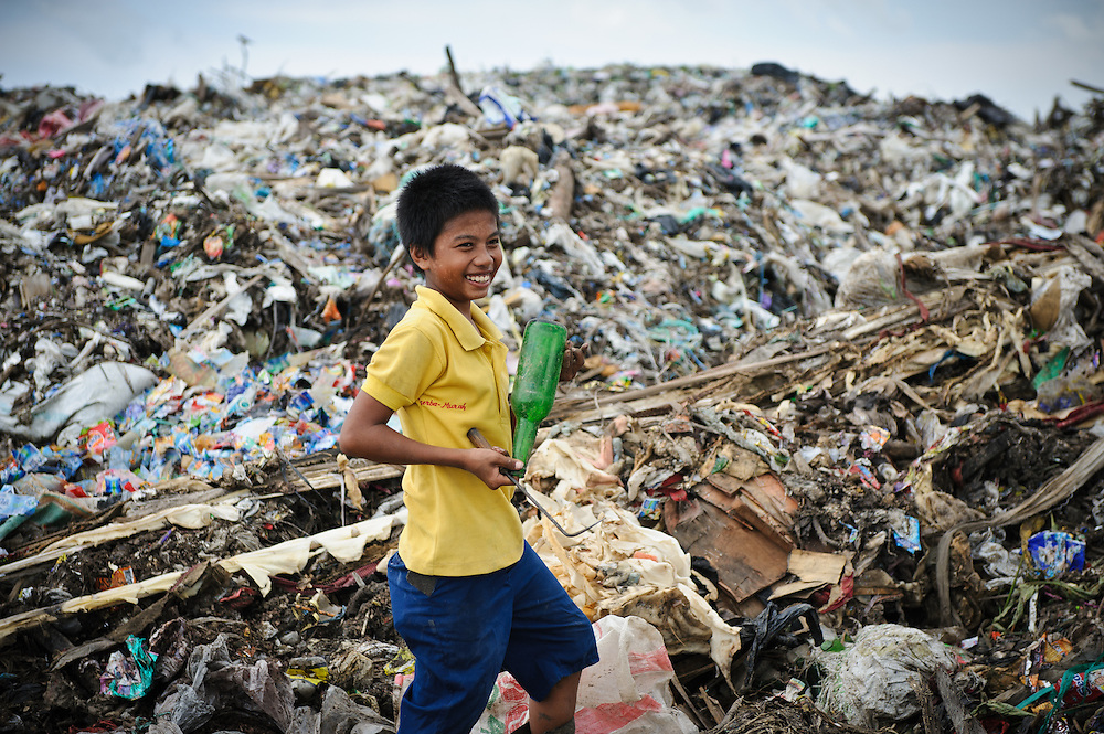 Taupik, 14, with an intact glass bottle at the 'Trash mountain', Makassar, Sulawesi, Indonesia.