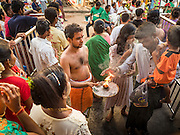 "22 OCTOBER 2015 - YANGON, MYANMAR: Hindus stand in the doorway of Sri Kali temple in Yangon to greet the goddess Durga on the last day of Navratri. Navratri, literally ""nine nights"" is a Hindu festival devoted to the Goddess Durga. Navratri festival combines ritualistic puja (prayer) and fasting. Navratri in India follows the lunar calendar and is celebrated in September/October as Sharad Navratri. It's widely celebrated in countries in Southeast Asia that have large Hindu communities, including Myanmar (Burma). Many of Myanmar's Hindus are descendants of Indian civil servants and laborers who came to Myanmar when it was the British colony of Burma.  PHOTO BY JACK KURTZ"