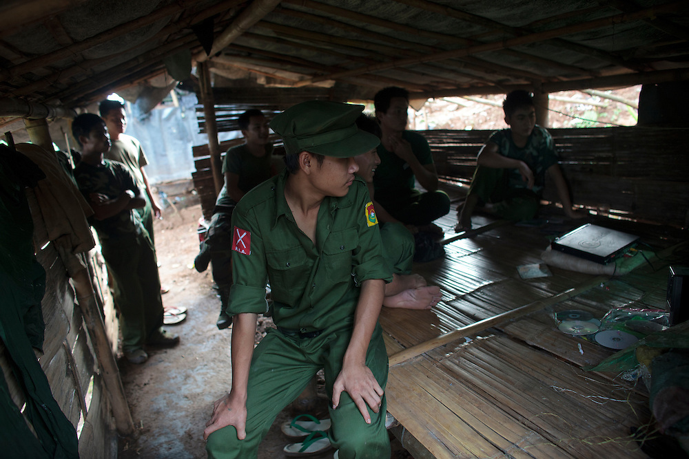 KIA's members watch TV in Naw Hpyu Post in the front line of the war against the Burma Government, Myanmar on August 2, 2012. The KIA formed in 1961 in response to a military coup in Burma led by General Ne Win, who attempted to consolidate Burmese control over regions on the periphery of the state which were home to various ethnic groups. From 1961 until 1994, the KIA fought a grueling and inconclusive war against the Burmese junta. In 2011, general Sumlut Gun Maw confirmed renewed fighting in the state of Kachin for independence. One of the new reasons for the ending of the ceasefire is the creation of the Myitsone Dam which requires the submergence of dozens of villages in Kachin state.