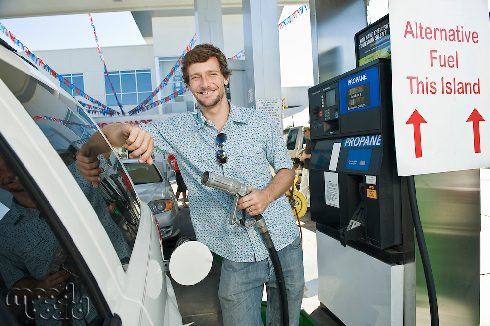 Portrait of smiling man refueling car at natural gas station