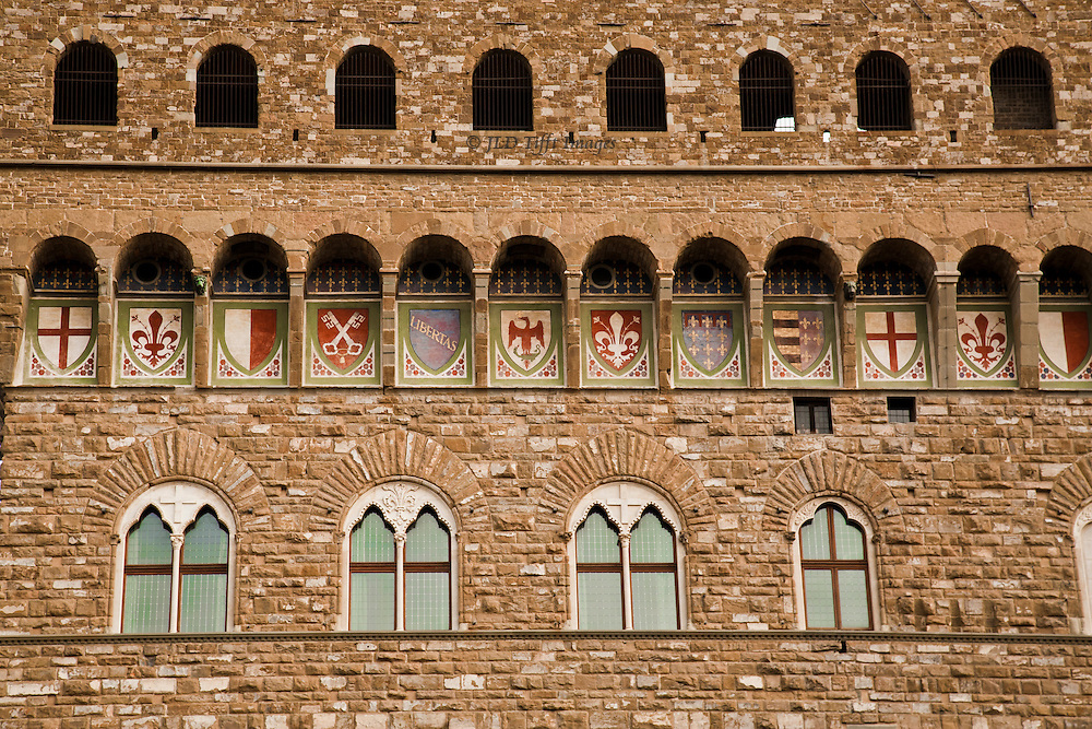 Upper facade of the Palazzo Vecchio, originally designed by Arnolfo di Cambio, completed 1322.  Coats of arms painted 1353.