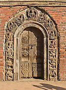 "Religious deities and symbols are carved in an ancient wood doorway in Patan's Durbar Square, Nepal, Asia. Patan was probably founded by King Veer Deva in 299 AD from a much older settlement. Patan, officially called Lalitpur, the oldest city in the Kathmandu Valley, is separated from Kathmandu and Bhaktapur by rivers. Patan (population 190,000 in 2006) is the fourth largest city of Nepal, after Kathmandu, Biratnagar and Pokhara. The Newar people, the earliest known natives of the Kathmandu Valley, call Patan by the name ""Yala""  (from King Yalamber) in their Nepal Bhasa language. UNESCO honored Patan's Durbar Square (Palace Square) as one of the seven monument zones of Kathmandu Valley on their World Heritage List in 1979. All sites are protected under Nepal's Monuments Preservation Act of 1956."