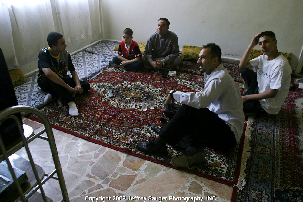 Clockwise from front, Emad Al-kasid, his brothers Hussein, 15, Aladdin, 8, his father Malik, and brother Sagid, 17, watch the first official meeting of Iraq's new government in his father's apartment in the Iraqi area of Damascus, Syria, Sunday, July 13, 2003. Al-kasid has been planning has been planning the trip home to Nasiriyah, Iraq, over the last year. He is visiting his immediate family is in Damascus, Syria, as hundreds of thousands of Iraqi Shiite settled in Syria after the Gulf War and their uprising against Saddam Hussein in 1991.
