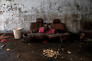 BEIRA, MOZAMBIQUE - JUNE 26, 2016: <br /> A boy sleeping on the couch in his &quot;house&quot; at the hotel entrance. Many residents do not have rooms. The building has 3 floors with 122 rooms.
