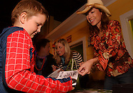 WDTN's Pam Elliot (right) hands an autographed photo to a young fan as Jim Bucher talks with Holly Samuels .during Howl-O-Ween 2010 at the Boonshoft Museum of Discovery in Dayton, Saturday, October 23, 2010..