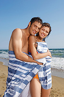 Young couple on beach wrapped in towel portrait
