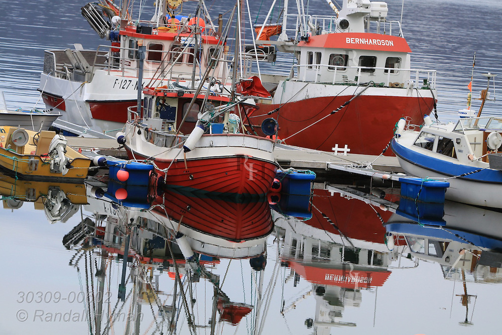 Fishing boats reflect in glassy surface of harbor in village of Kamoyvaer on Mageroya Island, Finnmark, Norway.