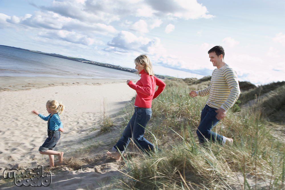 Parents and daughter (5-6) running onto beach