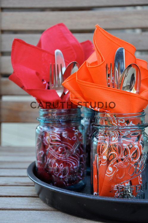 Bandannas wrapped around silver flatware place settings tucked into vintage mason jars