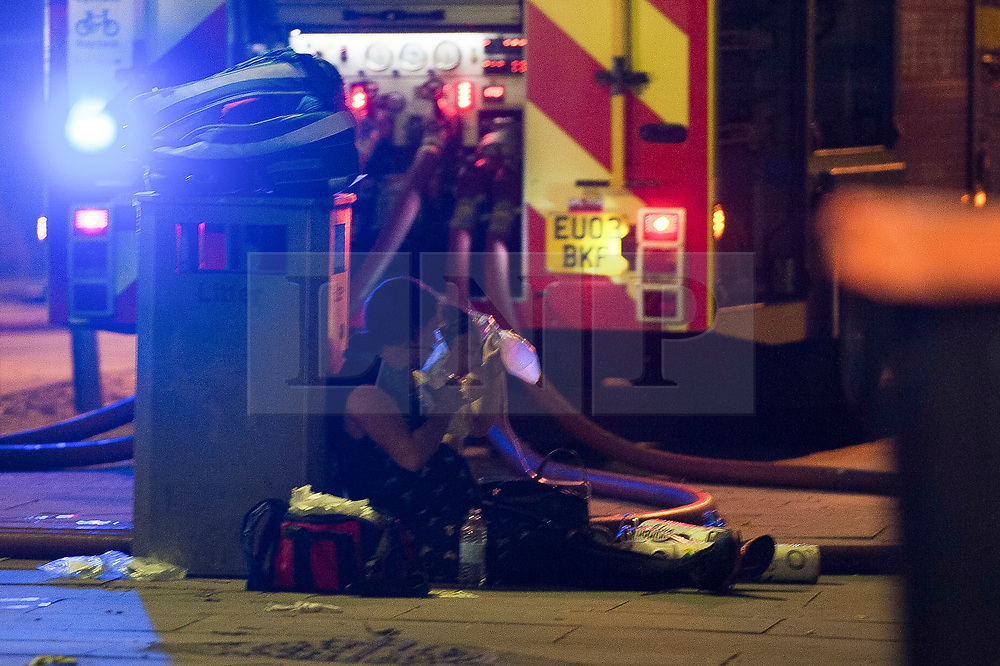 © Licensed to London News Pictures. 14/06/2017. London, UK. Members of the public receive treatment at the scene of a huge fire at Grenfell tower block in White City, London. The blaze engulfed the 27-storey building with 200 firefighters attending the scene. There were reports of people trapped in the building. Photo credit: Guilhem Baker/LNP