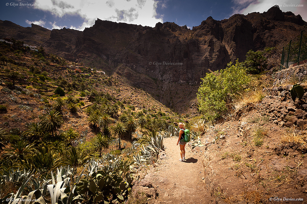 Fit blonde woman starting the famous and difficut hiking trail down the Masca Barranco Gorge in Tenerife which leads from the high mountain village of Masca down to the Atlantic Ocean at Masca Beach.