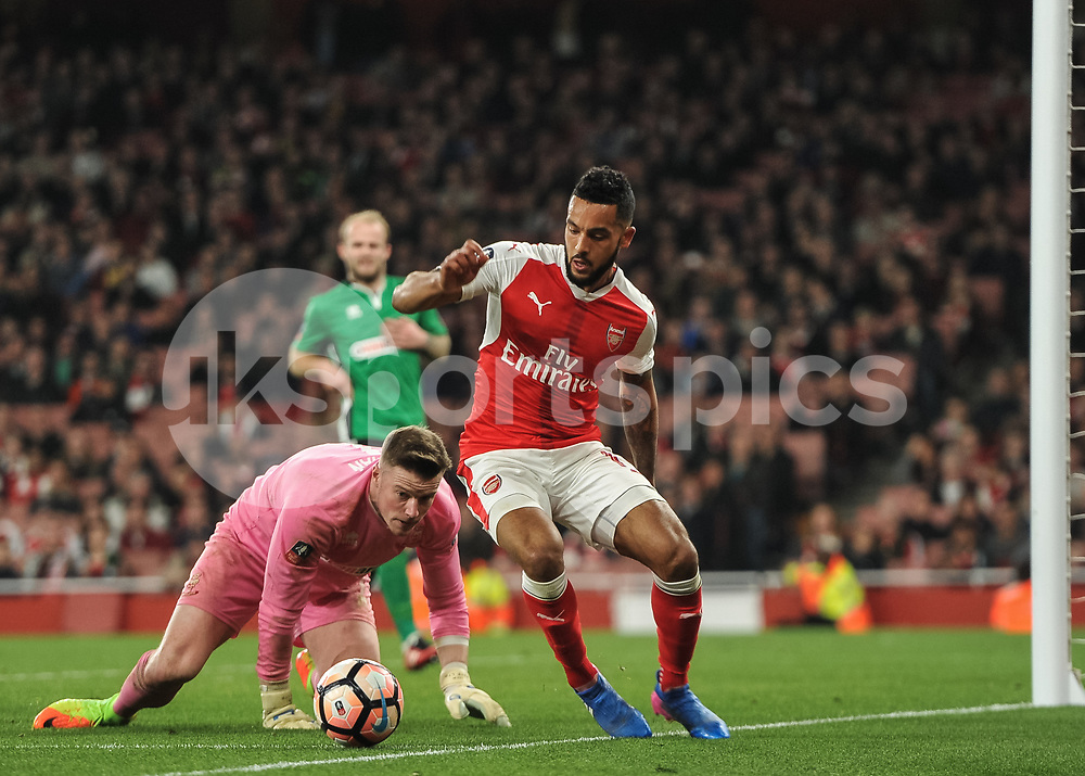 Theo Walcott of Arsenal and Paul Farman of Lincoln City battles for possession off the ball during the The FA Cup sixth round match between Arsenal and Lincoln City at the Emirates Stadium, London, England on 11 March 2017. Photo by Vince Mignott.