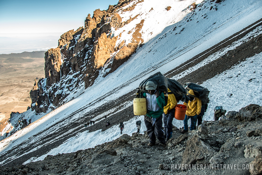 Porters walk up the steep, icy, and rocky trail of the Western Breach in the early morning hours on Mt Kilimanjaro.