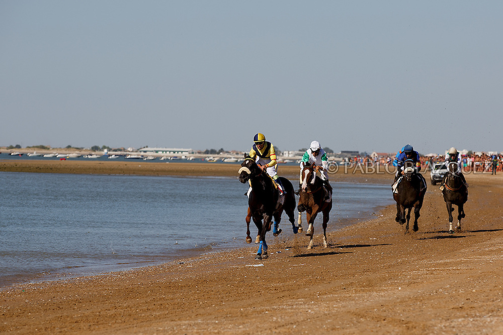 12/08/2016. Jockeys race their horses along the beach during the beach horse races on August 12, 2016 in Sanlucar de Barrameda, Cadiz province, Spain. Sanlucar de Barrameda yearly horse races traditional origin started with informal races of horse's owners delivering fish from the port to the markets. But the first formal races date back to 1845 and they are the second oldest in Spain, after Madrid. The horse races take place near the Guadalquivir river mouth during August