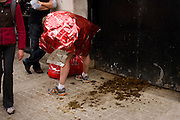 A marathon runner in insulating foil bends over manure left at Horseguards, appearing deceptively to have been at fault.