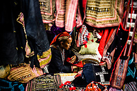 A Red Dzao woman sells embroidered clothes and bags at the market in Sapa in northern Vietnam.