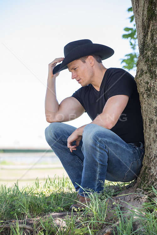 hot cowboy by a tree on a ranch