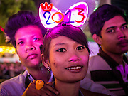 "31 DECEMBER 2012 - BANGKOK, THAILAND:  Thai teenagers at the New Year's Eve Party in Ratchaprasong Intersection in Bangkok. The traditional Thai New Year is based on the lunar calender and is celebrated in April, but the Gregorian New Year is celebrated throughout the Kingdom, especially in larger cities and tourist centers, like Bangkok, Chiang Mai and Phuket. The Bangkok Countdown 2013 event was called ""Happiness is all Around @ Ratchaprasong."" All of the streets leading to Ratchaprasong Intersection were closed and the malls in the area stayed open throughout the evening.   PHOTO BY JACK KURTZ"
