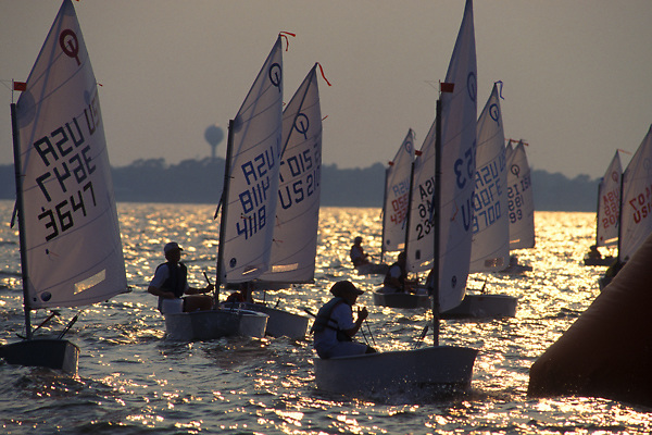 Stock photo of a group of sailboats on the water at sunrise