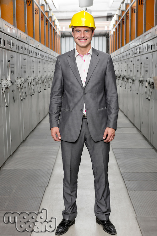 Full length portrait of smiling young male supervisor standing in control room