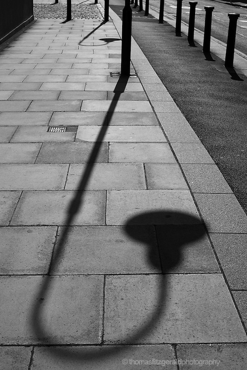 On a dublin footpath, the low morning sun casts the long shadow of a traditional street light on the pavement