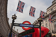 British flags hanging over London's Regent Street and the London Underground sign at the Piccadilly Circus station.