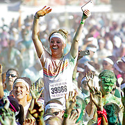"Participants of the Color Run Orlando event react to getting covered by the colored dust after completing the 5K.  Billed as the ""Happiest 5K on the Planet,? the Color Run is a family-friendly run for those who don't mind getting dust thrown at them after beginning the race with a plain white t-shirt on. This is the first event of the season and occured at the Citrus Bowl in downtown Orlando, Florida on January 13, 2013. (AP Photo/Alex Menendez)"