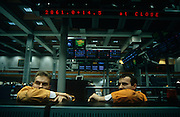 Two brokers working at the London International Financial Futures Exchange (LIFFE) have finished trading for the day and are resting chatting to colleages beneath a large old-fashioned dot matrix sign telling us the market's value at the close of business. They both wear orange jackets denoting their respective employers. They sit on the trading floor, otherwise known as the Pit where Derivatives, Options, Futures and their contracts are exchanged in a frenzy of arm and hand expressions which communicate prices and quantities. The LIFFE exchange was synonymous with Thatcherite capitalist money-making ethos in the City of London of the 80s and early 90s before the takeover by Euronext in January 2002. It is currently known as Euronext.liffe. Euronext subsequently merged with New York Stock Exchange in April 2007.