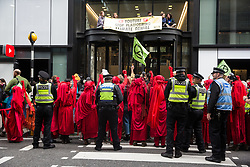 London, UK. 16 October, 2019. Extinction Rebellion's Red Brigade joins the International Rebellion Autumn Uprising 'No Social Media in a Dead Society' protest outside the headquarters of YouTube against the US video-sharing company's role in 'enabling the spread of systematic disinformation on climate change and the ecological crisis'.