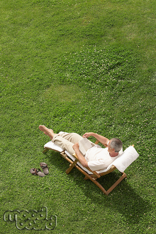 Middle-aged man reclining on lawn in deck chair reading high angle view