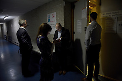 "© London News Pictures. ""Looking for Nigel"". A body of work by photographer Mary Turner, studying UKIP leader Nigel Farage and his followers throughout the 2015 election campaign. PICTURE SHOWS - Nigel and his team (l-r) personal assistant Lizzy Vaid, Election strategist Chris Bruni-Lowe and Adam from his security team, wait to go out and speak to the assembled UKIP supporters at a public meeting in the Carn Brae Leisure Centre in Cornwall, on March 6th 2015. . Photo credit: Mary Turner/LNP **PLEASE CALL TO ARRANGE FEE** **More images available on request**"