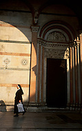 Nun passing by Lucca's Duomo.
