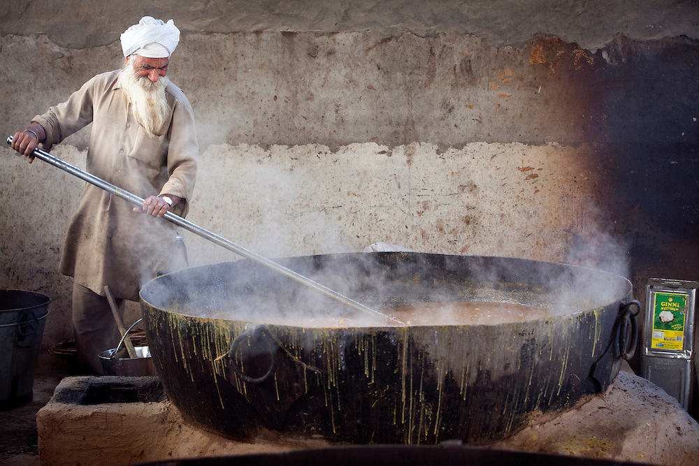 A cook in a Sikh kitchen cooking in an extremely large pot.<br />