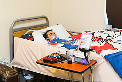 Jamie Baskaran who suffers from degenerative muscular dystrophy, lies in his bed in his Star Wars themed bedroom in the sheltered accommodation in which he lives. He is now confined to bed having been told that his wheelchair presents a health and safety risk. Leatherhead, Surrey, December 05 2018.
