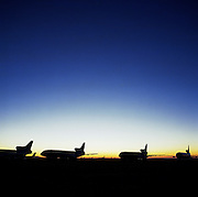 Fading, graduated light of the arid Sonoran desert shows the remains of airliners at the storage facility at Mojave, California, their silhouettes forming a line of aviation's by-gone era. Because of age or a cooling economy they are either cannibalised for still-working parts or recycled for scrap, their aluminium fuselages worth more than their sum total. After a lifetime of safe commercial flight, wings are clipped and cockpits sliced apart by huge guillotines, cutting through their once-magnificent engineering. Picture from the 'Plane Pictures' project, a celebration of aviation aesthetics and flying culture, 100 years after the Wright brothers first 12 seconds/120 feet powered flight at Kitty Hawk,1903...