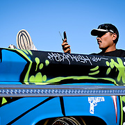 Omar Dominguez, of Indio, California, lounges in the back of his vintage, grafitti'd Ford truck, making a phone call during the Dr. George Car Show, held at the Indian Wells Tennis Garden in Indian Wells, California, on February 14, 2009. Omar and his friends painted the entirely grafitti covered vehicle themselves.  Photo by Jen Klewitz
