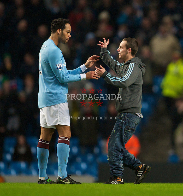 MANCHESTER, ENGLAND - Tuesday, January 18, 2011: A Manchester City supporter invades the pitch and confronts Joleon Lescott during the FA Cup 3rd Round Replay match against Leicester City at the City of Manchester Stadium. (Photo by David Rawcliffe/Propaganda)