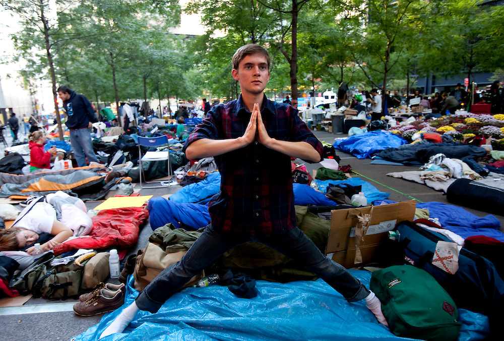 "Nathaniel Dolton-Thornton, 19, from Santa Cruz, CA, stretches in Zuccotti Park. Dolton-Thornton came to Zuccotti Park in a bus of fellow Wesleyan University students on October 7.  He is amazed by what he describes as ""people living in a whole alternative community.""  Nathaniel commented on the relative peace and calm he observed during his stay, and believes that some of the inspiration for the protest comes from recent revolutions known collectively as the Arab Spring."