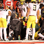 Ducks' Deforest Buckner and Marcus Mariota express concern to their injured TE Pharaoh Brown after Mariota's 4 Quarter TD.  The University of Oregon Ducks defeated the University of Utah Utes 51-27 at Rice-Eccles Stadium, Salt Lake City, Utah. Photo by Barry Markowitz, 11/8/14, 8pm