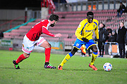Arthur Gnahoua of Kidderminster Harriers takes on Mark Carrington of Wrexham during the Vanarama National League match between Wrexham AFC and Kidderminster Harriers at the Glyndŵr University Racecourse Stadium, Wrexham, United Kingdom on 23 February 2016. Photo by Mike Sheridan.