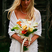 A bride looks down at her natural bouquet.