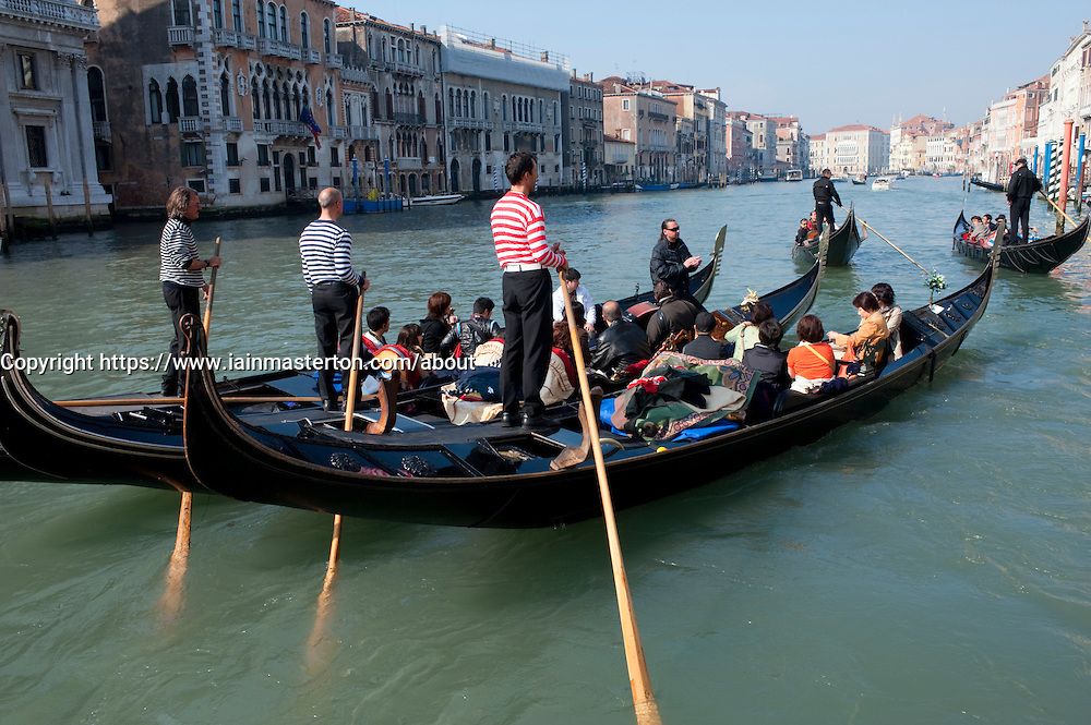 Gondolier singing opera arias to Japanese tourists in Gondolas on the Grand Canal in Italy