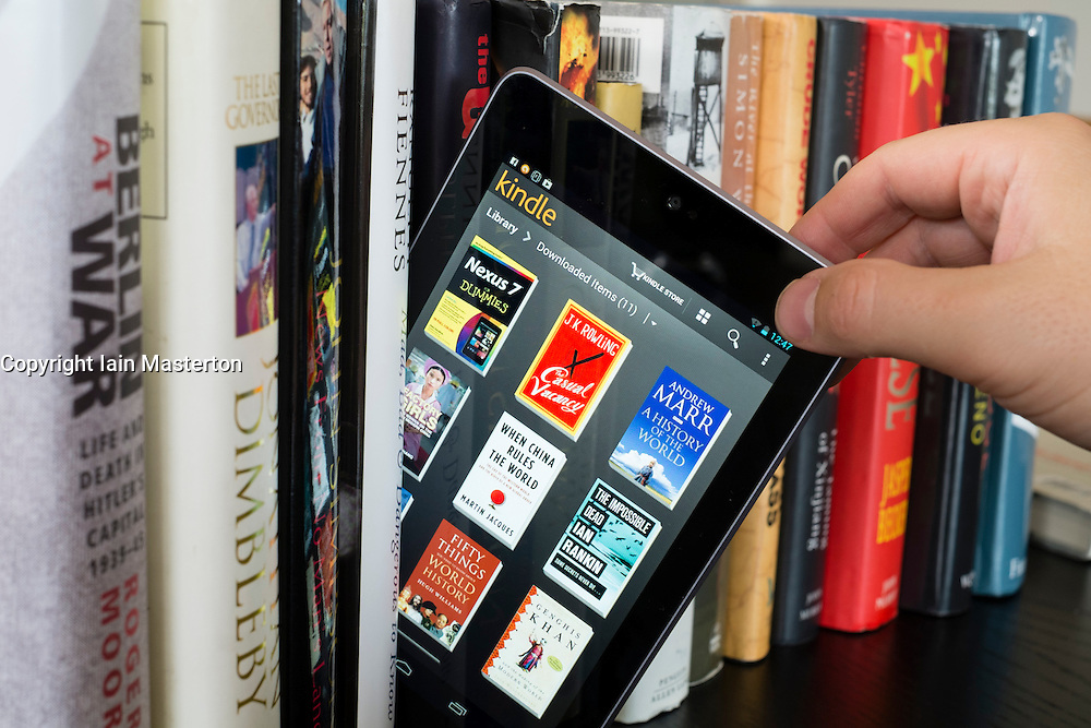 Google Nexus 7 tablet computer with kindle e-book library application and shelf of traditional hardback paper books