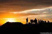 After a long day out in the water, friends gather at sunset atop a dune for dinner.  Ocean Beach, San Francisco, California.