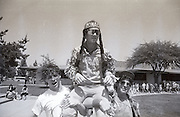 A high schooler dressed as the Monache High School Mascot, which was chosen by hippies when the school opened in the early 1970s, a Marauder, is carried during homecoming week activities during which time a home coming king and queen will be chosen in Porterville, California in the spring of 1989. Such a mascot is no longer politically correct.