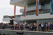 Spectators greeting racing yachts at days end stand in front of Veles e Vents, or Sails and Winds, the main building dominating Port America's Cup with its modernistic architecture perched at the harbor entrance; Valencia, Spain.